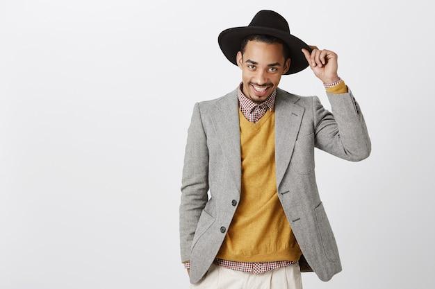 Meine damen, wie geht es ihnen? porträt des koketten hübschen afroamerikanischen mannes, der hut hält und mit leidenschaftlichem blick salutiert, breit lächelt, zuversichtlich ist, während schöne frau begrüßt