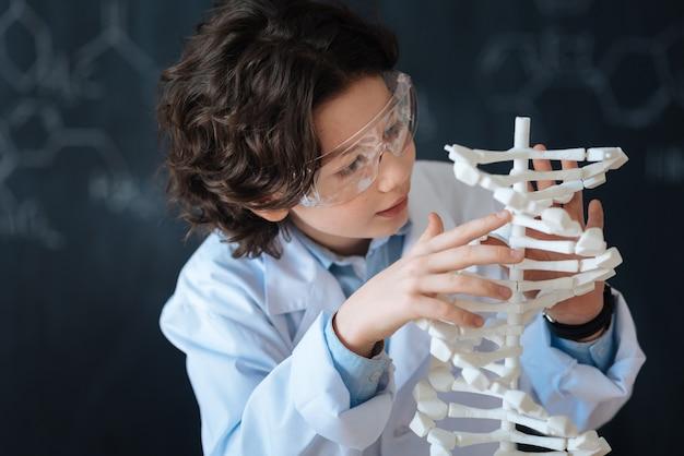 Meine fähigkeiten üben. konzentrierter, kluger, neugieriger schüler, der in der schule vor der tafel steht, während er das chemieprojekt studiert und daran arbeitet