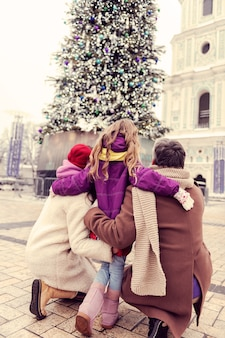 Meine familie. charmantes blondes kind, das ihre eltern umarmt, während es auf weihnachtsbaum starrt