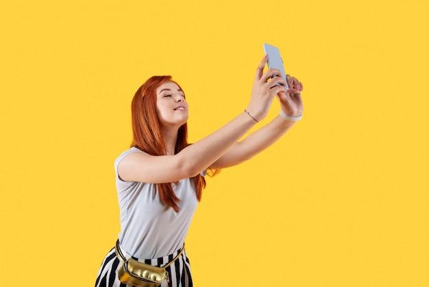 Meine fotos. attraktive charmante frau, die ihr smartphone hält, während sie selfies nimmt