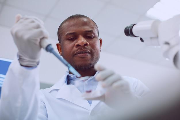 Meine inspiration. konzentrierter qualifizierter wissenschaftler, der eine blutuntersuchung durchführt und eine uniform trägt