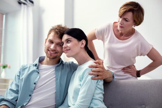 Meine liebe frau. angenehmer glücklicher mann, der seine frau umarmt, während er mit ihr auf dem sofa sitzt