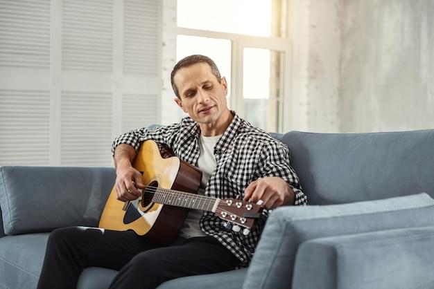 Meine lieblingsgitarre. hübscher glücklicher gut gebauter mann, der lächelt und gitarre spielt, während er auf der couch sitzt