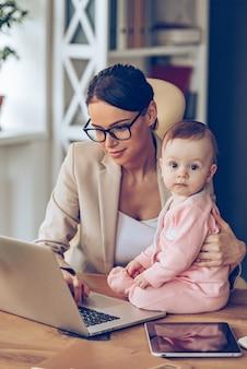 Meine mama ist eine echte expertin! kleines baby, das in die kamera schaut, während sie mit ihrer mutter im büro auf dem schreibtisch sitzt