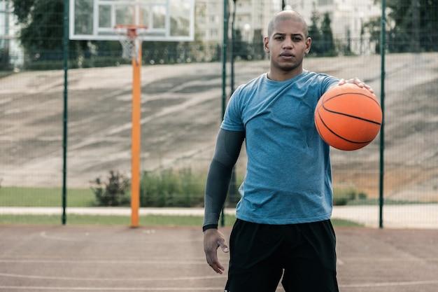 Meine passion. hübscher gut gebauter mann, der auf dem basketballplatz steht, während er sie ansieht