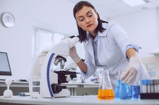 Meine verantwortung. schöner erfahrener wissenschaftler, der mit einem mikroskop arbeitet und die röhren berührt