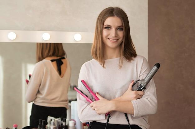 Meister der frisurenfrau mit einem arbeitsgerät flach für das verdrehen des haares