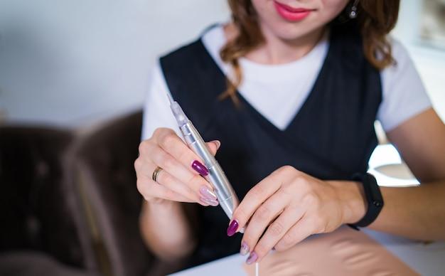 Meister des permanent-tattoos mit werkzeug für microblading, training in permanent make-up auf falschen lippen.