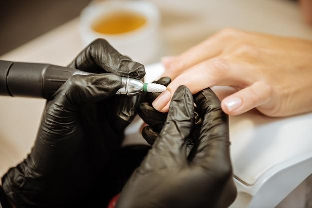 Meister in handschuhen. nahaufnahme des erfahrenen maniküremeisters, der schwarze handschuhe trägt, die nägel polieren