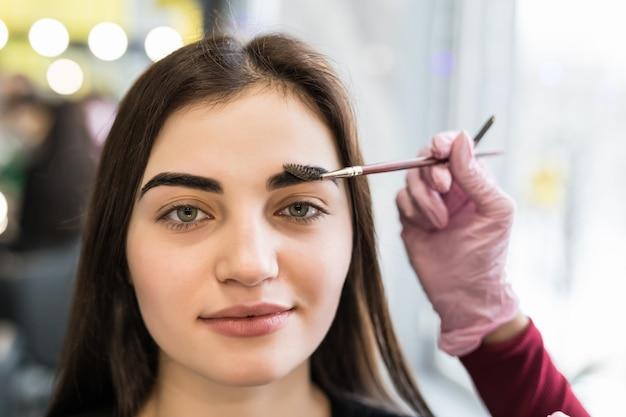 Meister macht die letzten schritte im make-up für das modell mit grünen augen