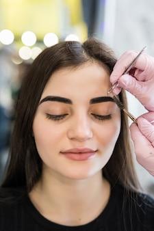Meister macht die letzten schritte im make-up-verfahren für ein modell mit grünen augen