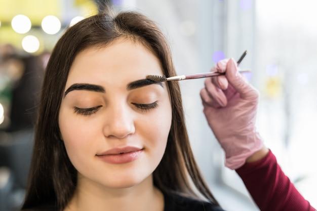 Meister macht letzte schritte im make-up für das modell mit geschlossenen augen