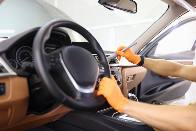 Meister-mechaniker in handschuhen, der den luftkanal des autos mit bürsten-nahaufnahme-auto-detaillierungsservice säubert