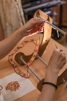 Meister mit dekorativem teppichband im atelier