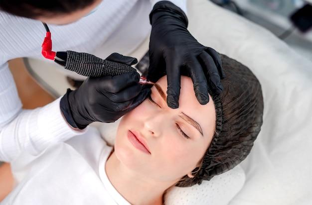 Meister mit professioneller microblading-maschine mit tinten und nadel, die schöne augenbrauen dauerhaft schminken