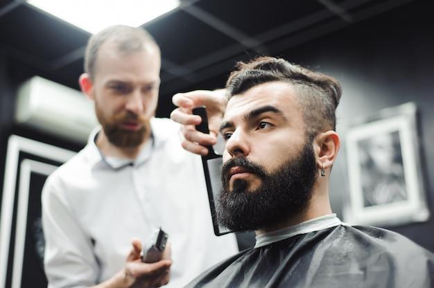 Meister schneidet haare und bart von männern im friseursalon, friseur macht frisur für einen jungen mann.