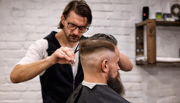 Meister schneidet haare und bart von männern im friseursalon, friseur macht frisur für einen jungen mann