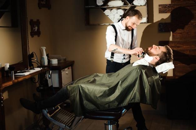 Meister schneidet haare und bart von männern im friseursalon