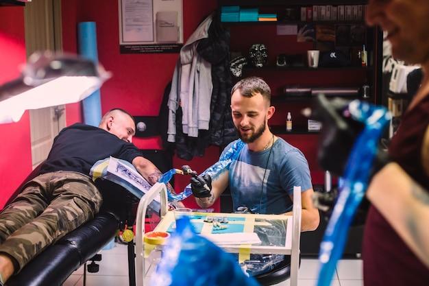 Meister und klient im tätowierungsstudio