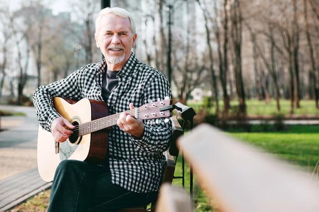 Meisterakkord. netter reifer mann, der kamera betrachtet und gitarre spielt