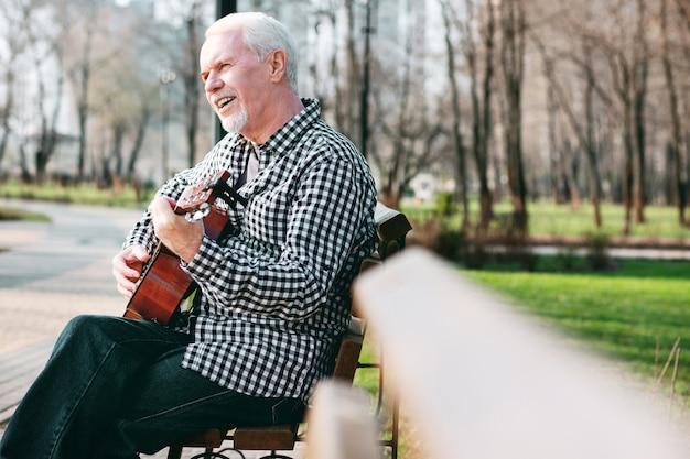 Meistergitarre. ansprechender reifer mann, der lied lernt und gitarre spielt
