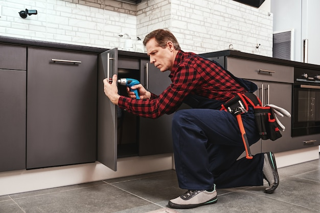 Meisterhand arbeitet in voller größe von einem älteren handwerker, der küchenschränke repariert repair