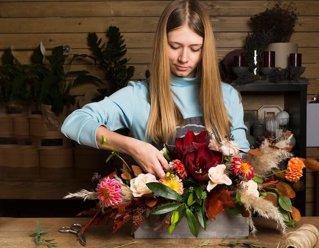 Meisterklasse der floristin bei der arbeit mit blumenstrauß. frau, die blumenstrauß von verschiedenen herbstblumen macht. porträt des geschäftsfrauenfloristen am blumenladen