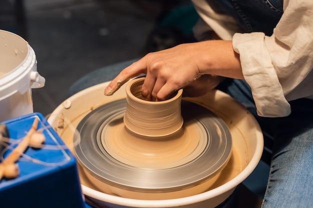 Meisterkurs über das formen eines topfes in einer kunstwerkstatt. das mädchen hinter der töpferscheibe macht mit den händen einen rohling.