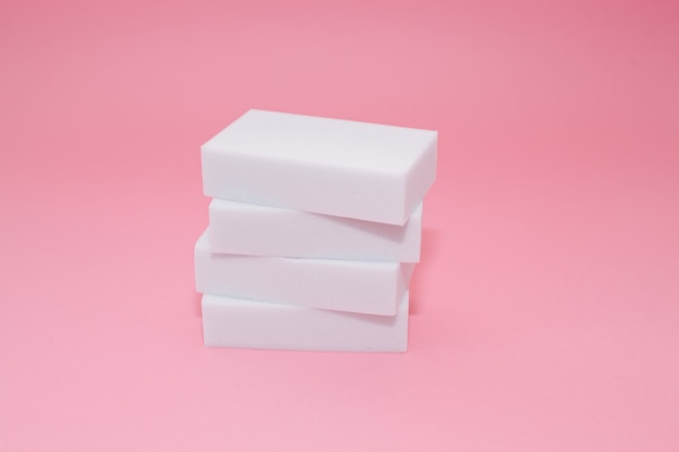 Melaminhaushalts-schwammstapel mit vier schwämmen für das säubern auf rosa hintergrund.