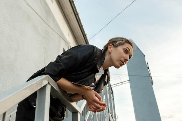Melancholische einsame junge frau in der schwarzen lederjacke, die auf treppe mit wand auf hintergrund aufwirft. einsamkeit.