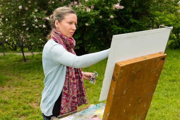 Melancholische malerin malt ein meisterwerk auf einem bock und staffelei während eines kunstunterrichts im freien