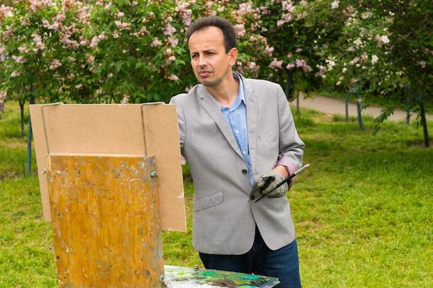 Melancholischer männlicher maler, der ein meisterwerk auf einem bock malt und staffelei während eines kunstunterrichts in einem park malt