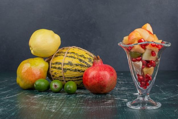 Melone, granatapfel, quitten und feijoa mit tasse apfel