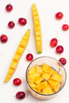 Melone im mixbecher in stücke schneiden. geschnittene melone und kleine rote äpfel auf dem tisch. weißer hintergrund. flach liegen