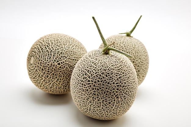 Melone mit drei kantalupen auf weiß