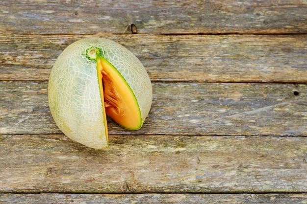 Melone mit scheiben und blättern auf altem holztisch.