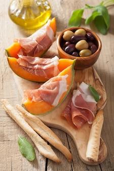 Melone mit schinken-grissini-oliven. italienische vorspeise