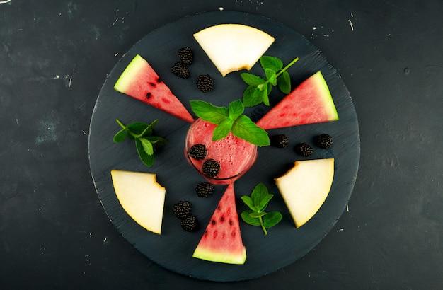 Melone, wassermelone, brombeeren und minze auf einem holztisch