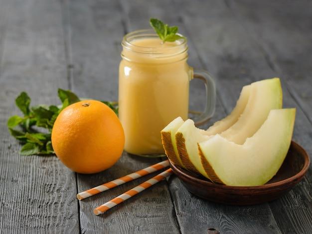 Melonen-smoothies, minze, orangefarbene cocktailröhrchen auf einem holztisch.
