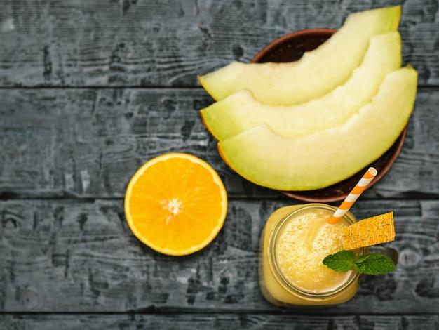 Melonen-smoothies und melonenscheiben auf einer tonschale und orange auf einem schwarzen holztisch. der blick von oben. flach liegen.