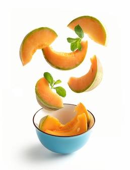 Melonenscheiben der cantaloupe mit fliegenden minzblättern in einer blauen schüssel, lokalisiert vom weißen hintergrund