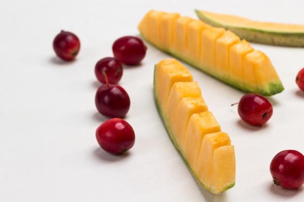 Melonenschnitze und kleine rote äpfel auf dem tisch. weißer hintergrund. draufsicht