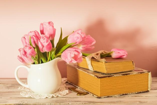 Memo-stillleben mit büchern, schlüssel und rosa tulpen