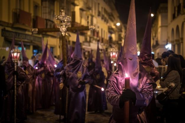 Menge in kostümen in semana santa festival in sevilla gefangen genommen