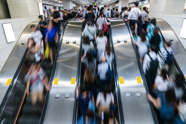 Menge von den fußgängern unerkennbar, die in rolltreppe am hauptverkehrszeitmorgen vor arbeitszeit in der u-bahn-transportnabe, hong kong, zentraler bezirk gehen