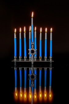 Menora mit blauen brennenden kerzen und reflexion auf oberfläche für chanukka jüdischen feiertag.
