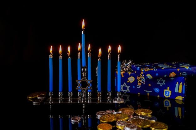 Menora mit blauen brennenden kerzen und schokoladenmünzen auf oberfläche für chanukka jüdischen feiertag.