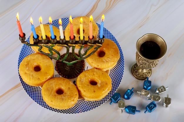 Menora mit brennenden kerzen, donuts und einer silbernen tasse wein