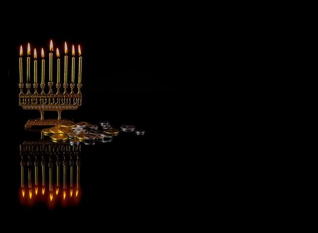 Menora mit goldenen brennenden kerzen, schokoladenmünzen und reflexion auf der oberfläche für chanukka jüdischen feiertag.
