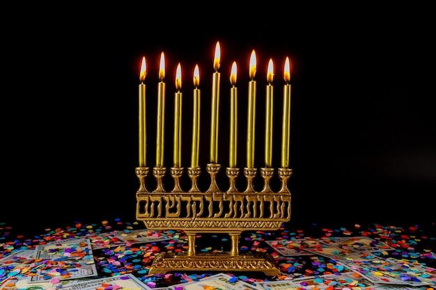 Menora und konfetti mit geld auf schwarzem hintergrund. jüdisches feiertags-chanukka-symbol.